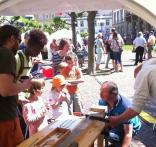 Das TEam der Holzwerkstatt beim Austesten der Belastbarkeit von Furnierholz vor den Augen neugieriger Kinder